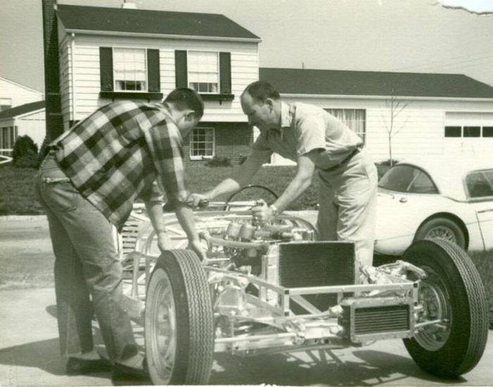 father and son work on a classic car